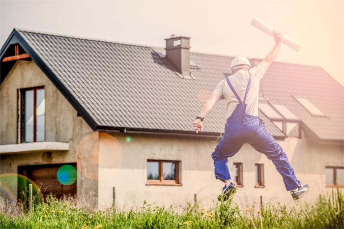 Mitarbeiter mit Bauplan macht einen Luftsprung vor dem Rohbau